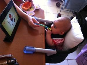 Beatriz comendo e assistindo à Galinha Pintadinha